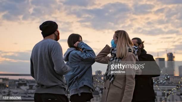 réunion d'amis pendant la pandémie du coronavirus. des bosses de coude. coucher du soleil sur le toit - éviter de se serrer la main photos et images de collection