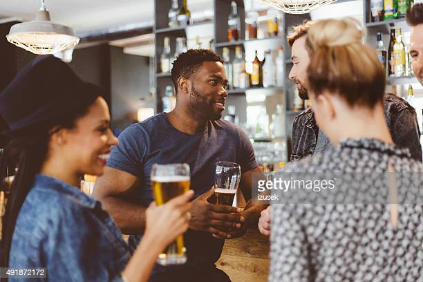Friends meeting in a pub, drinking beer
