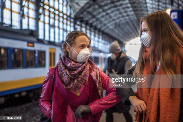 friends meeting in public during virus outbreak - railway station stock pictures, royalty-free photos & images