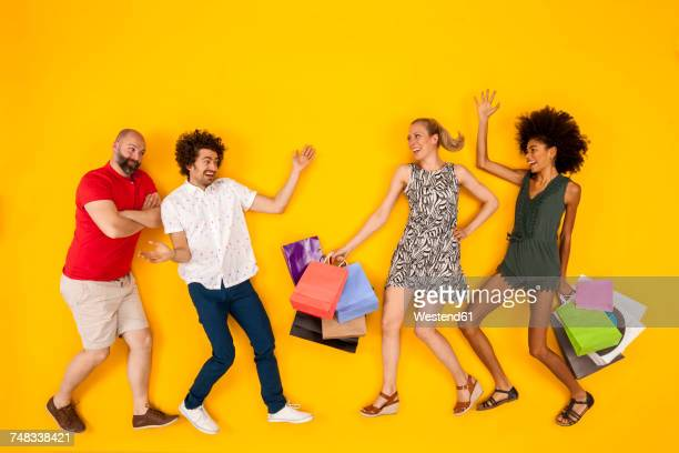 Friends meeting women carrying shopping bags