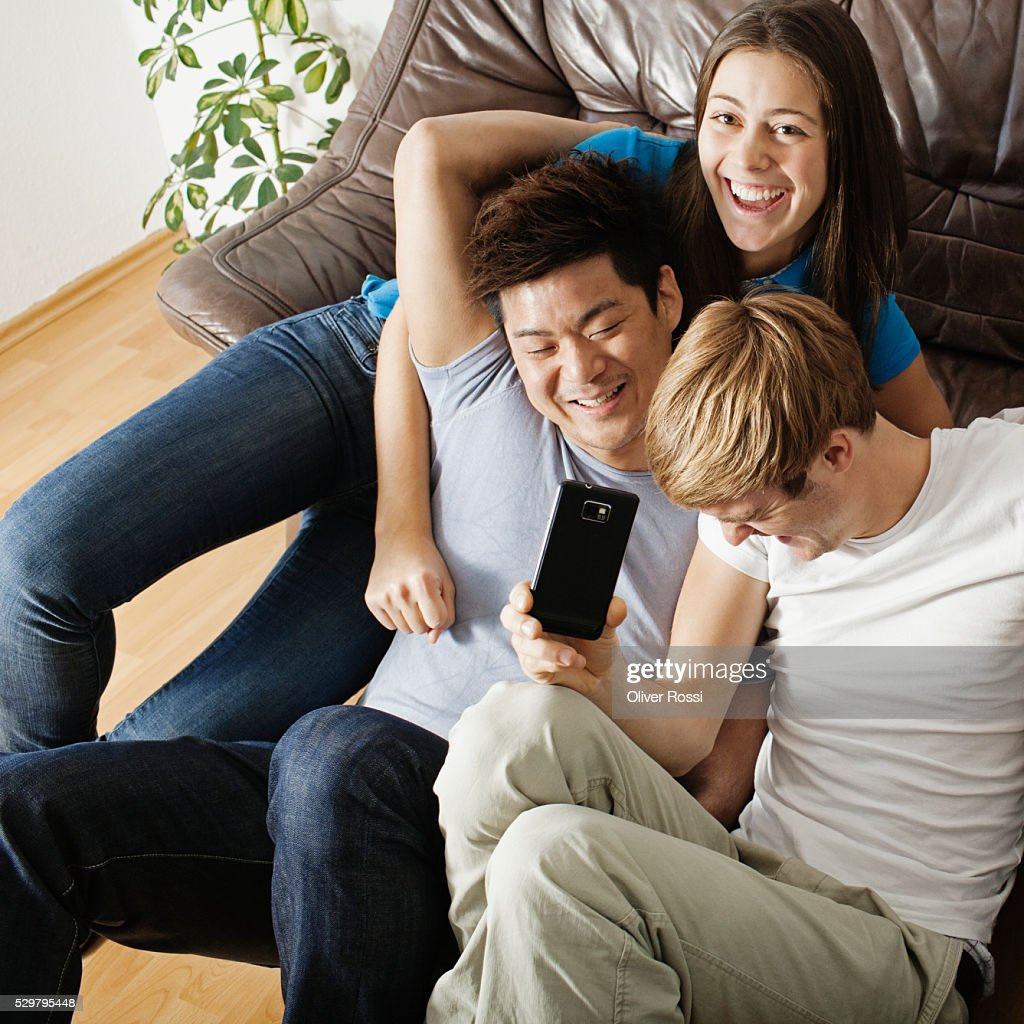 Friends messing about in living room : Stock Photo