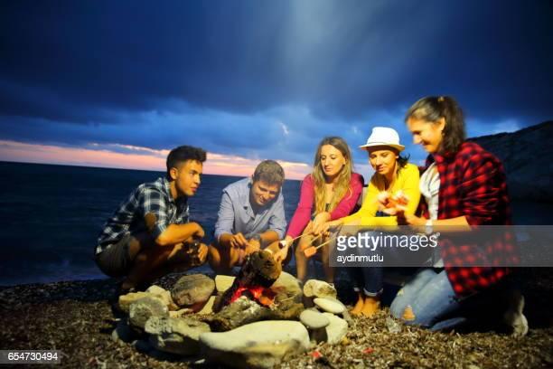 Friends near campfire