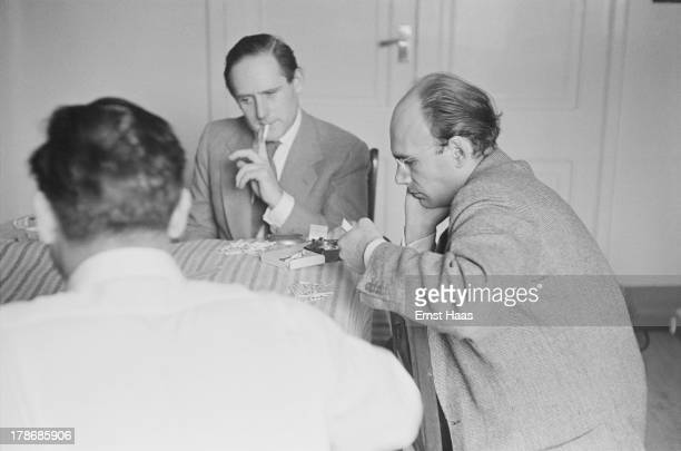 Friends of American film director and screenwriter John Huston play cards for matches on the hospital bed during a visit to Huston in hospital 1953...