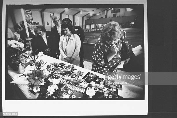 Friends of drug voodoo mass murder victim Mark Kilroy pass by table covered w flowers boyhood snapshots of him following his memorial service at Our...