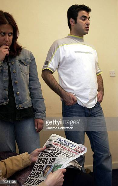 Friends of Iranian Kurdish refugee Abas Amini sit with him as he sits in his home in protest with his eyes mouth and ears sewn shut May 28 2003 in...