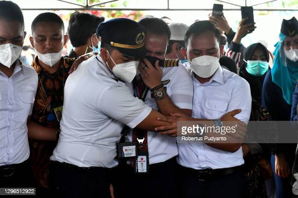 Friends of Sriwijaya Flight Officer Fadly Satrianto comfort each other as they attend his funeral ceremony at Keputih cemetery on January 15, 2021 in...