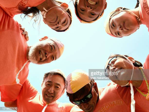 friends of the life saver team are laughing with their heads folded and shoulders crossed. - active lifestyle stock pictures, royalty-free photos & images