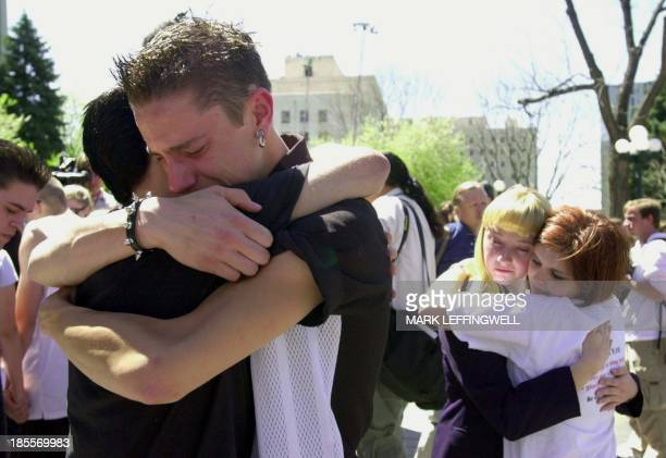 Friends of the victims of the 20 April 1999 Columbine High School shooting embrace after the moment of silence observed statewide during a ceremony...