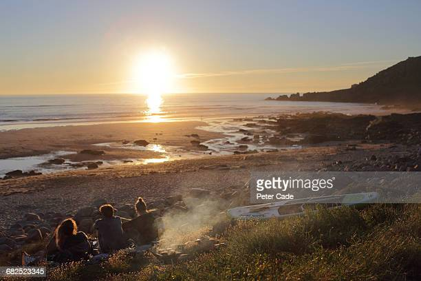 friends on beach at sunset - dusk stock pictures, royalty-free photos & images