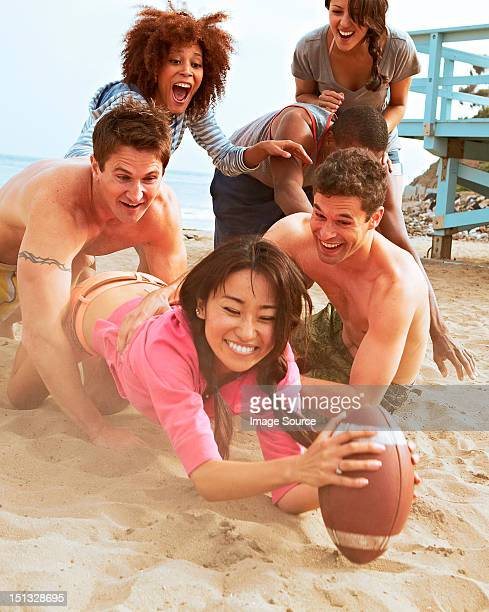Friends on beach playing rugby
