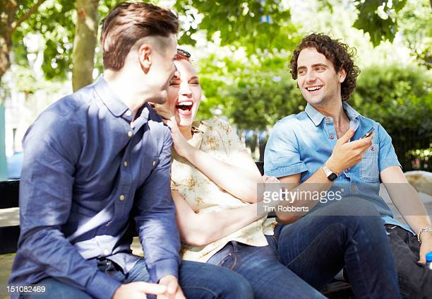 friends on bench laughing with smart phone. - three people stock pictures, royalty-free photos & images