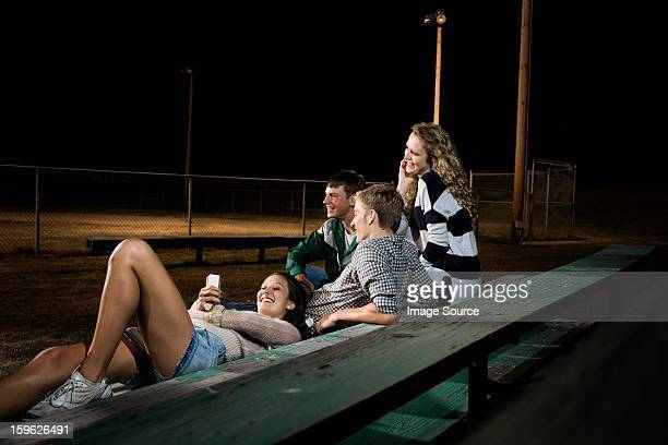 Friends on bleachers at night, girl using cell phone