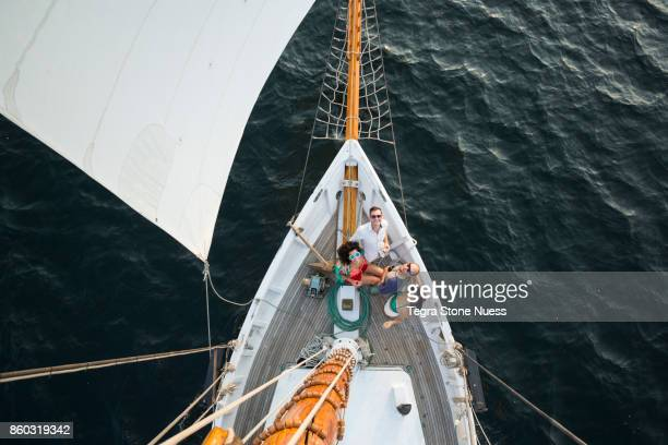 Friends on bow of large sailboat from above