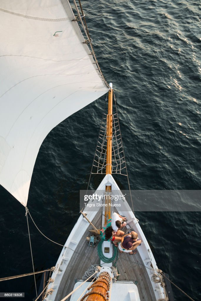 Friends on bow of large sailboat : Stock Photo