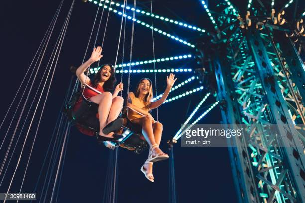 friends on chain swing ride - amusement park ride stock pictures, royalty-free photos & images