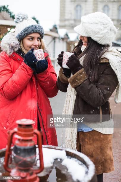 Freunde auf Weihnachtsmarkt trinken Punsch