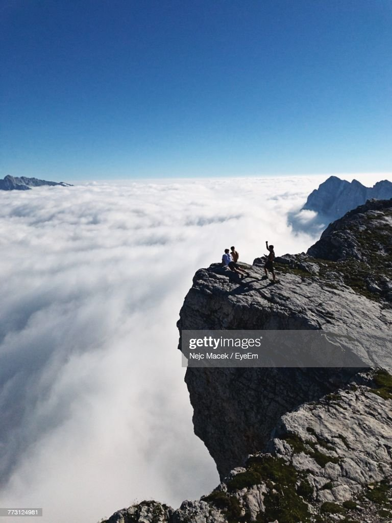 Friends On Cliff Against Sky : Photo