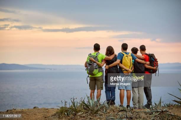 amis sur la falaise regardant la mer pendant le coucher du soleil - cinq personnes photos et images de collection