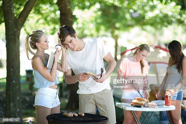 Friends on holiday grilling sausages and listening to music on a digital tablet