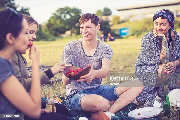 Friends on picnic eating strawberries