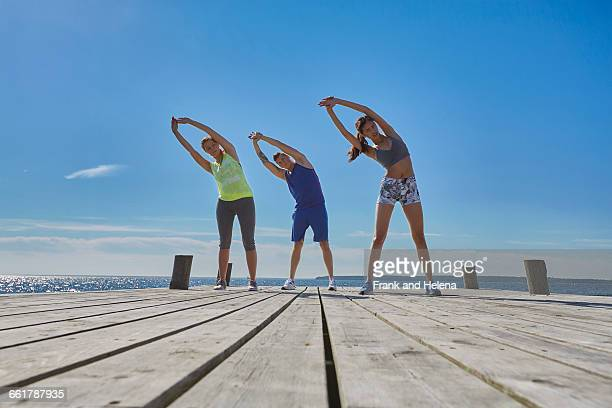 Friends on pier side by side arms raised bending over sideways stretching