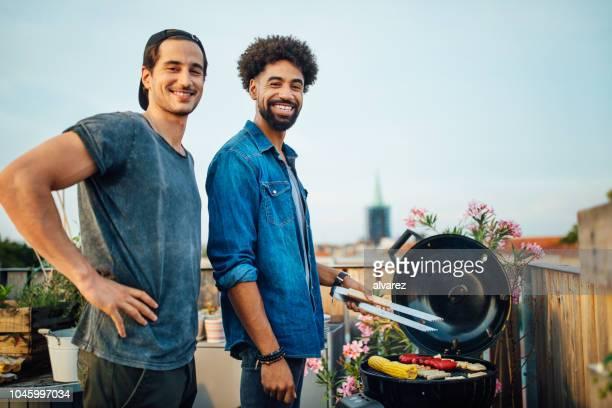 freunde auf dach, die zubereitung von speisen auf grill - grill zubereitung stock-fotos und bilder