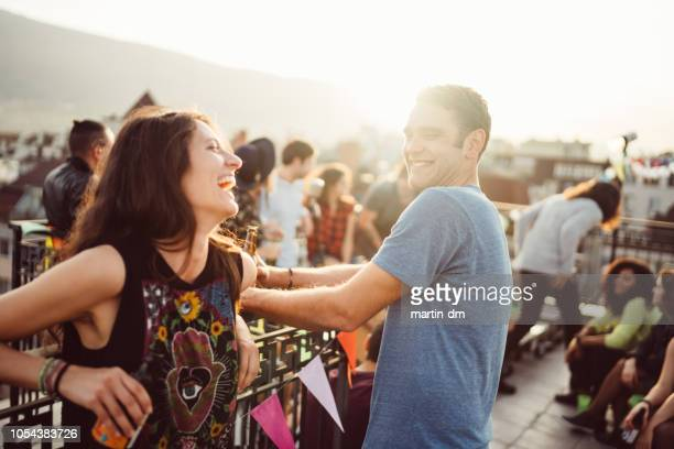 friends on rooftop party - flirting stock pictures, royalty-free photos & images