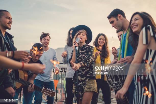 friends on rooftop party - karaoke stock pictures, royalty-free photos & images