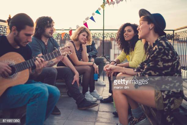 friends on rooftop party - martin guitar stock photos and pictures