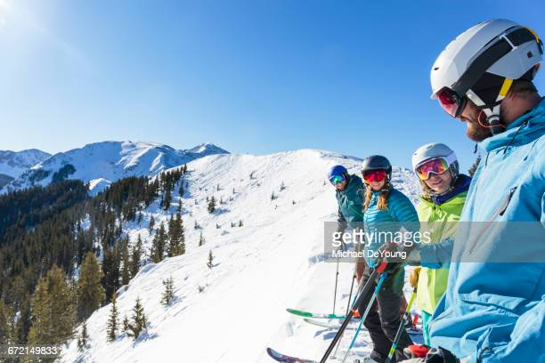 Friends on skis standing on snowy mountaintop