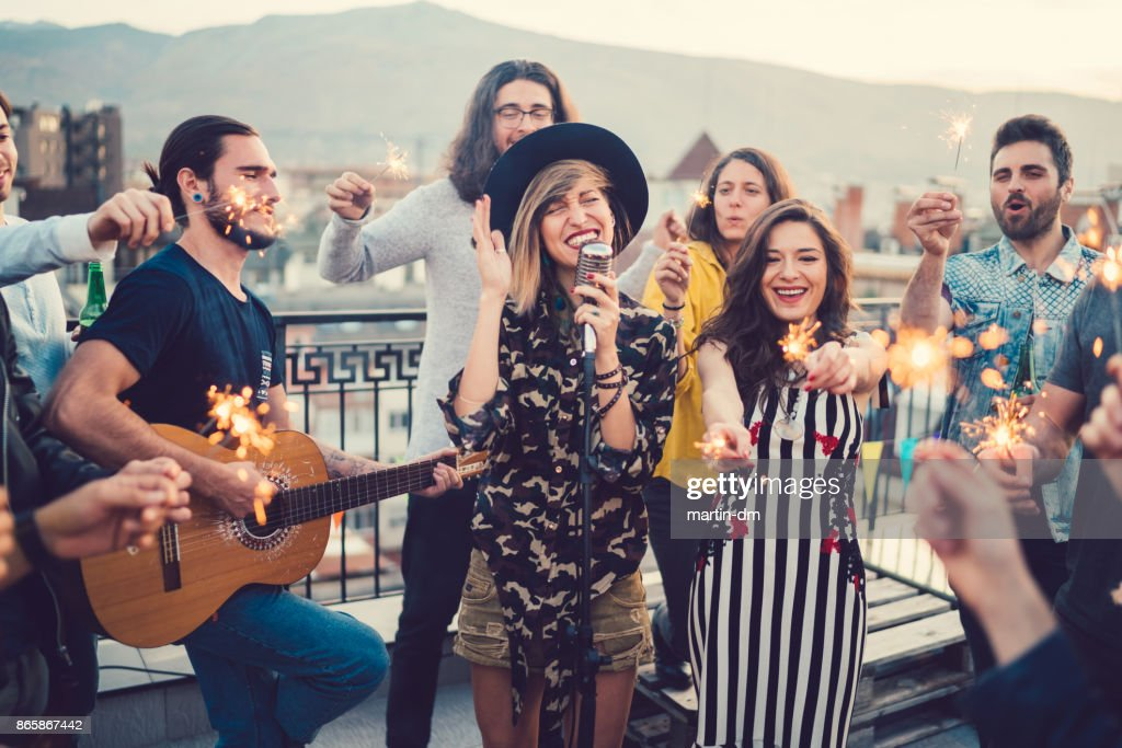 Friends on the rooftop listening to a music band : Stock Photo