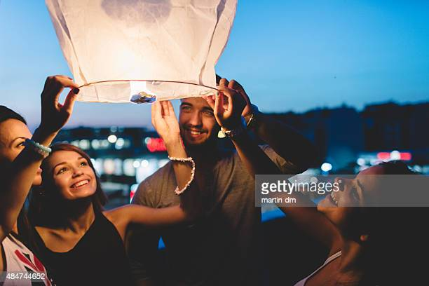 friends on the rooftop releasing paper lantern in the sky - releasing stock pictures, royalty-free photos & images