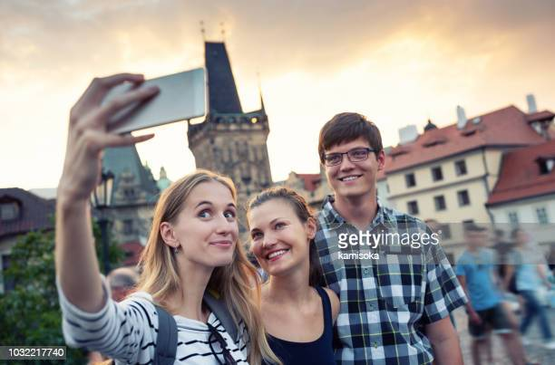 friends on vacation taking selfie - charles bridge stock pictures, royalty-free photos & images