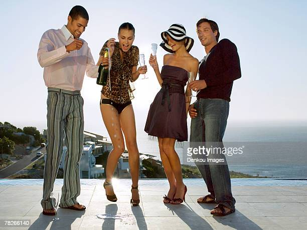 friends opening a bottle of champagne. - open blouse stock photos and pictures
