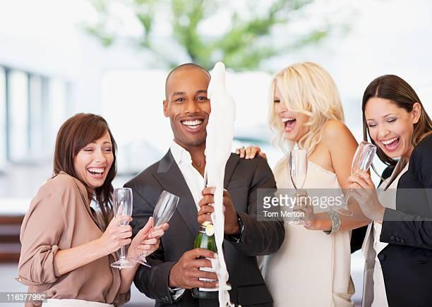 Amis ouvrir une bouteille de champagne