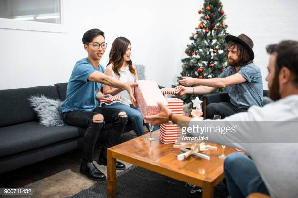 freunde, die weihnachtsgeschenke zu öffnen - gift lounge stock-fotos und bilder
