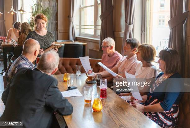 friends ordering food in a british pub - pub stock pictures, royalty-free photos & images