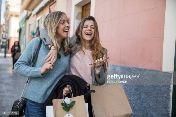 friends out shopping and laughing in street - girlfriend stock pictures, royalty-free photos & images
