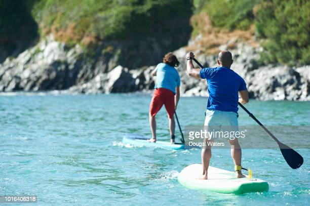 friends paddle boarding at sea on an atlantic coastline. - paddling stock pictures, royalty-free photos & images