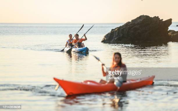 friends paddling along coastline of mediterranean at dawn - sea kayaking stock pictures, royalty-free photos & images