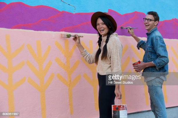 Friends painting mural wall outdoors