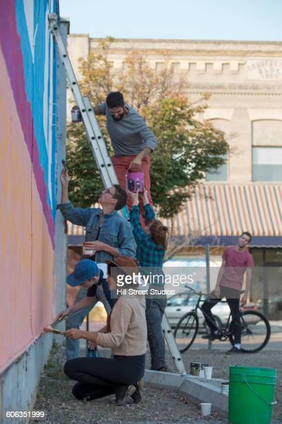 friends painting mural wall outdoors - pintar mural fotografías e imágenes de stock