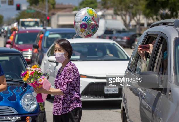 Friends parade by and cheer on Mildred ``Millie'' Stratton during a caravan of cars led by the Alhambra Police and Fire past her home celebrating her...