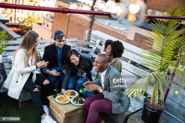 friends party on a rooftop in new york manhattan - aperitif stock photos and pictures