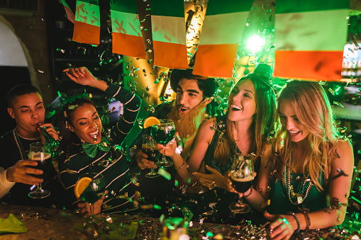 Friends partying with drinks and confetti on Saint Patrick's day 972154888