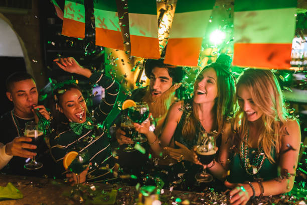 friends partying with drinks and confetti on saint patrick's day - irish pub foto e immagini stock