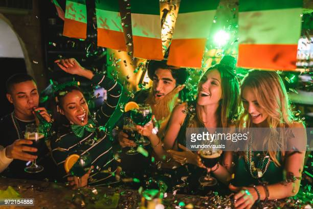 friends partying with drinks and confetti on saint patrick's day - st patricks day stock pictures, royalty-free photos & images