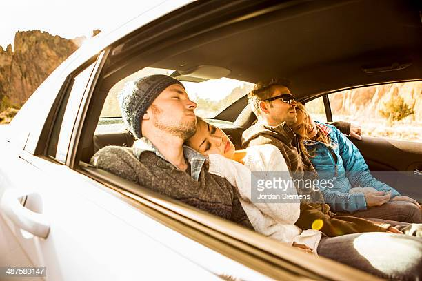 Friends passed out in the backseat of a car.