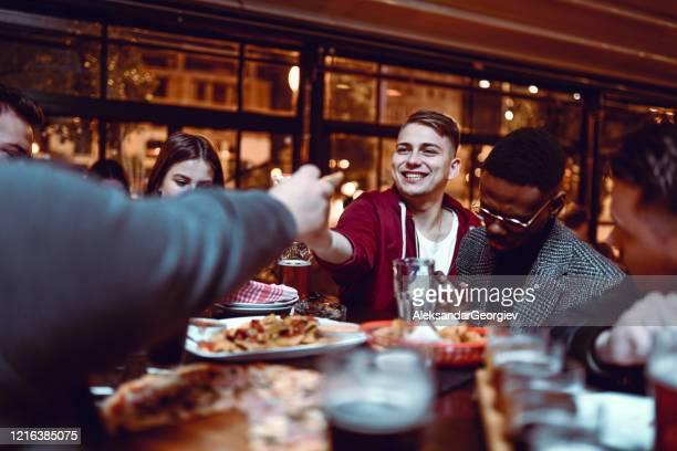 ピザの互いの部分を渡す友人 - 消毒用アルコール ストックフォトと画像