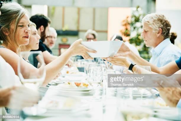 Friends passing serving bowl across table during celebration dinner on restaurant patio